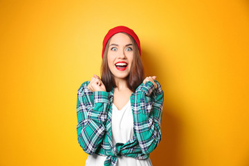 Excited hipster girl on color background
