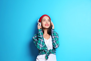 Attractive hipster girl with headphones on color background