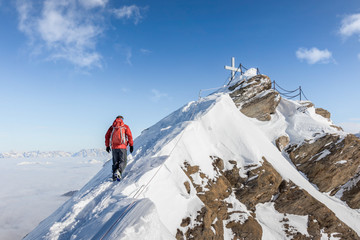 Aluminium Prints Mountaineering Mountaineer hiking up a snowy ridge in the alps