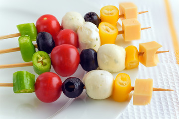 Appetizer on stick with various vegetables and cheese.