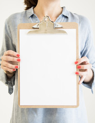 woman holding clipboard with white paper