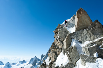 Climbing in Chamonix. Climber on the snowy ridge of Aiguille du Midi