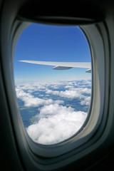 Blick aus einer Flugzeugkabine auf Wolkenlandschaft und Spitze der Tragfläche