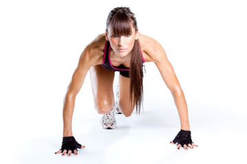 Fit and sporty young woman preparing for a run over white background.