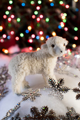 little lamb ornament in winter scene with bokeh lights