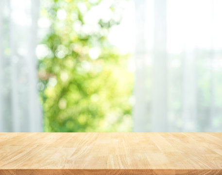 Empty of wood table top on blur of curtain with window view green from tree garden background.