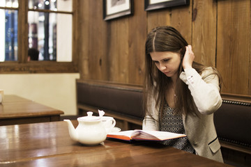 the girl sits in a cafe and reads a book, straightens her hair