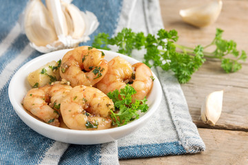 shrimps or prawns and garlic in olive oil with parsley garnish in a white bowl, blue napkin on a rustic wooden table, spanish tapas appetizer gambas al ajillo