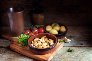 Tapas bowl with shrimps or prawns in garlic olive oil, potatoes, tomatoes and herbs on a rustic wooden table, spanish appetizer, dark background with cop space