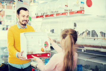 Male store assistant offering cage with canary bird