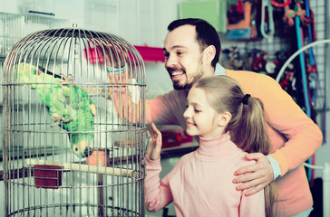 father and daughter excited to see green parrot in pet shop