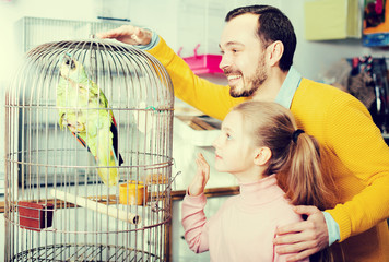Father and daughter admiring large green parrot