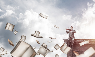 Handsome violinist play his melody and books flying around