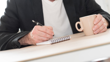 Man taking writing on a notebook