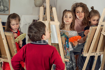 Children paint paint on canvas