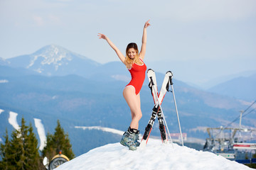 Happy beautiful female skier wearing red bodice, posing with skis and poles on the top of the mountain. Winter ski resort, forests, ski slopes and ski lift on the background