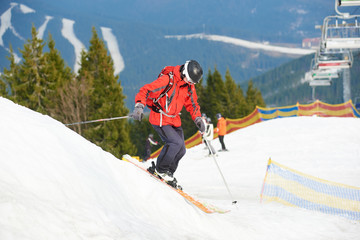 Man skier skiing on the snowy slope at ski resort in the mountains. Forests, ski slopes and ski lift on the background. Ski season and winter sports concept