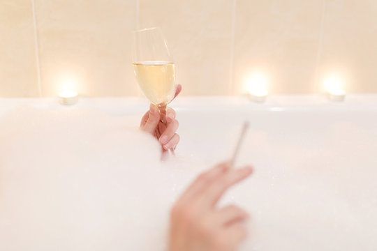 Close up photo of young sexy woman with clean health skin lying in white foam bath tub with candles around in light bathroom, drink alcohol from wine glass and smoke cigarette indoors.