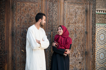 Arab couple in relationship talking and smiling in traditional clothing