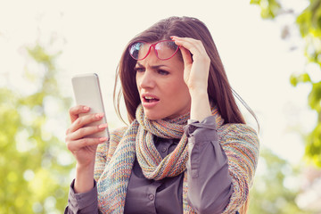 Annoyed upset woman in glasses looking at her smart phone with frustration while walking on a street