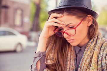 Stressed sad woman sitting outdoors. City urban life style stress