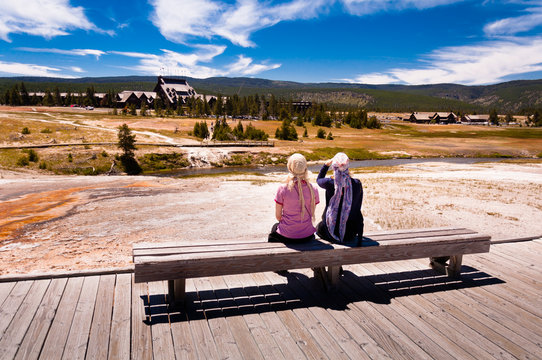 Two women sitting on a bench in the yellowstone national park