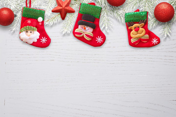 Sock waiting for Santa Claus Christmas gifts on whiteee wooden desk with decorations nad fir branches.