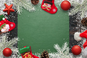 Christmas decorations, fir branches kid socks and pinecones composition with free space in the middle for text. Green tablecloth on table.