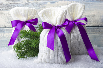 New Year bags with gifts on the snow. Surprise. Wooden background