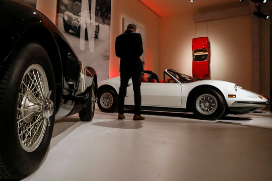 "A guest looks at a1974 Ferrari Dino 246 GTS by Scaglietti displayed during a media preview for the ""RM Sotheby's Icons"" sale at Sotheby's in New York"