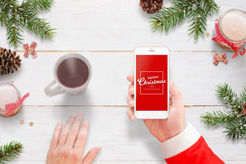 Santa Claus send Merry Christmas message with mobile phone. Hot tea, and Christmas decoration beside.