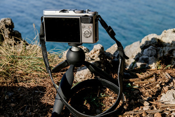 Camera on a small tripod on a mountain above the sea