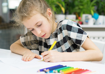 Little girl drawing with pencil at home.