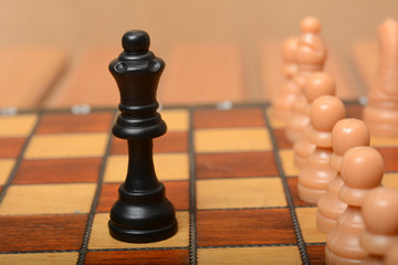 Queen Figure on chessboard with pawns in line