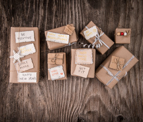 New Year goals written on gift boxes over rustic wood