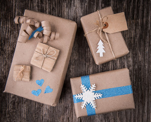 Closeup of boxes of gifts in natural paper rustic wooden table