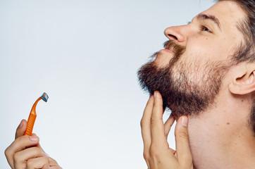 A man with a beard on a light background holds a razor, shaving, portrait