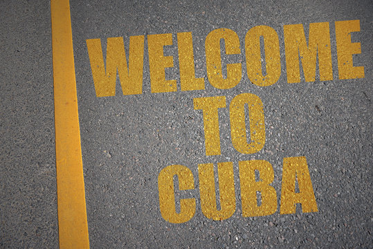 asphalt road with text welcome to cuba near yellow line.