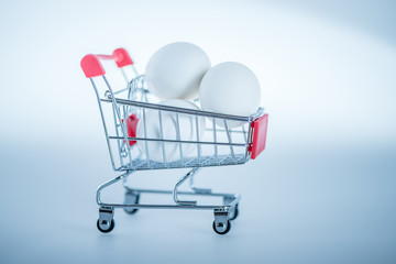 white eggs in a miniature shopping cart trolley against white background