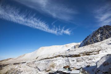 Зимний пейзаж. Красивые горы в снегу, белые облака на синем небе над живописным ущельем. Припрда Северного Кавказа