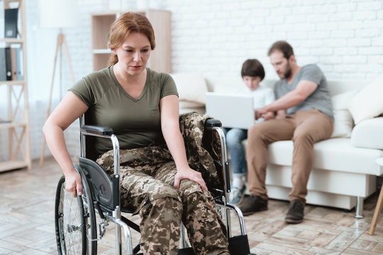 Woman veteran in wheelchair returned from army. A woman in a wheelchair is in pain. She's in military uniform.