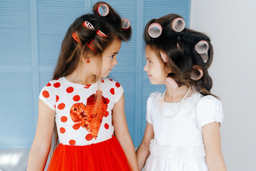 Close-up picture of cute little girls with hair curlers