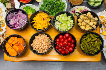 pickled tomatoes and cucumbers with mushrooms champignons and beans with sweet pepper and cucumber and carrots in plates near salads and cheese on the table, top view