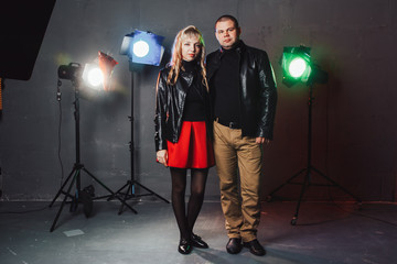Couple in black dresses during image shooting in studio and spotlights