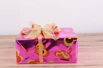 Christmas box gift pace on wood background.