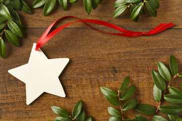 Handmade, star-shaped blank Christmas gift tag with red ribbon on rustic wood background with natural evergreen decorations. Simple, rustic, holiday crafts objects elements.