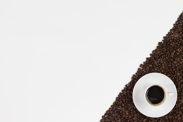 Cup of coffee and coffee beans on white background. Top view with space for your text.
