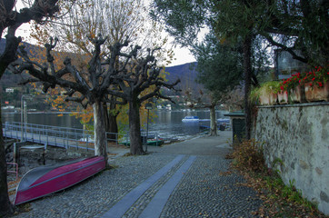 Pescatori Island, Italy pink boat between two bare trees, on a small cobblestone street overlooking Lake Maggiore