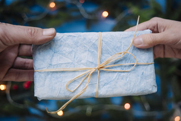 Giving a Christmas blue gift from hand to hand