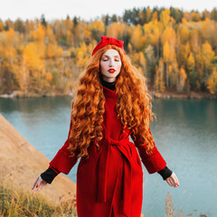 Red-haired woman with long curly hair in a red coat and a green turban on a bright autumn background. Girl on the background of a lake with blue water